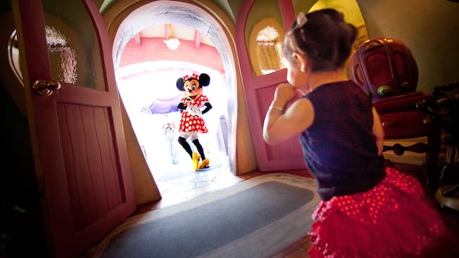 Minnie Mouse poses near a little girl