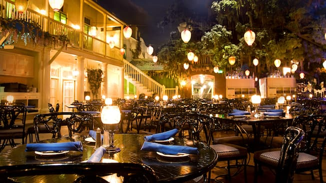A restaurant seating area with set tables, chairs and hanging lights