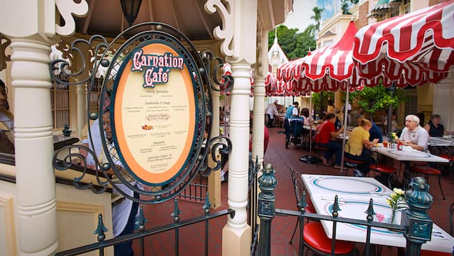 People in a restaurant seating area near a sign that reads Carnation Café