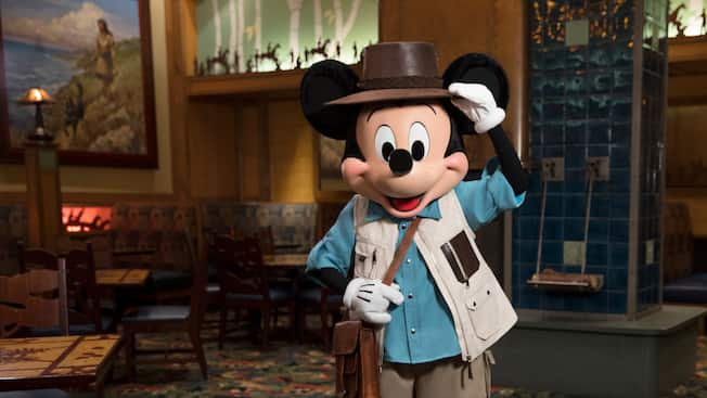 Mickey Mouse, dressed as an explorer, standing in a large dining room furnished in the style of a wilderness lodge