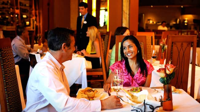 A man and woman smile at a table plated with food in a bustling restaurant