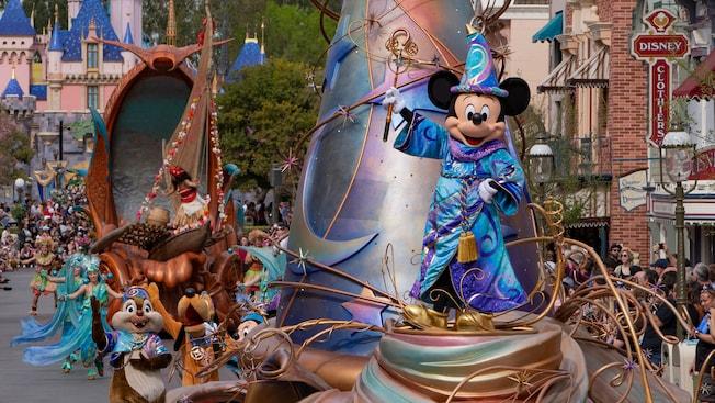 眠れる森の美女の城近くをパレードでするフロートに立つ魔法使いのコスチュームを纏ったミッキーマウス