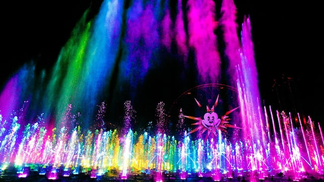 Colored lights shine on spouting fountains near Paradise Pier and Mickey's Fun Wheel