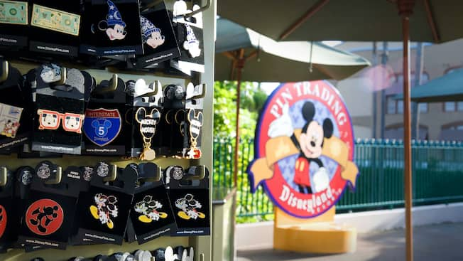 Decorative pins near umbrellas and a sign that reads Pin Trading Disneyland Resort