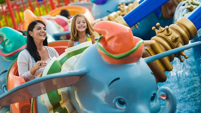 A mother and daughter ride aboard Dumbo The Flying Elephant
