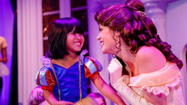 A little girl dressed as a princess smiles with Belle