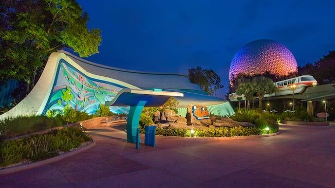 A Disney Monorail passes the lighted Spaceship Earth near The Seas with Nemo and Friends
