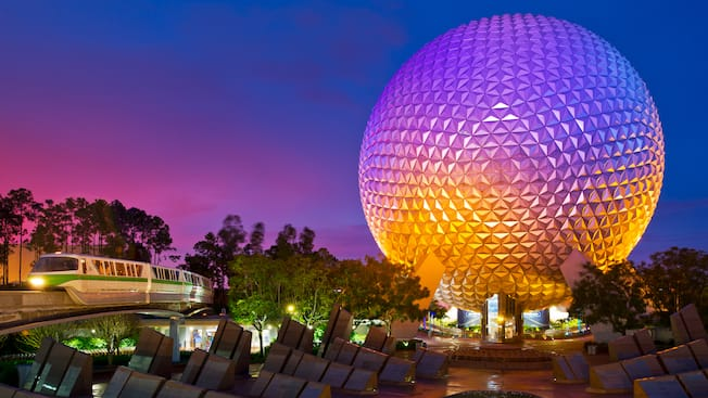 The Disney Monorail glides by the lighted Spaceship Earth