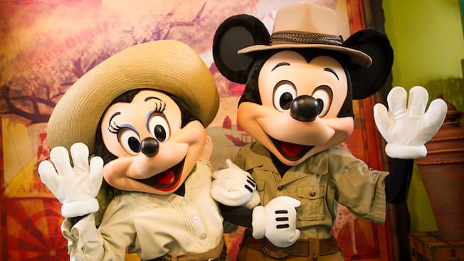 Mickey Mouse and Minnie Mouse, both wearing safari costumes, wave hello