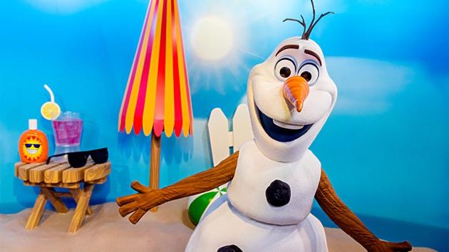 Olaf on a beach next to an umbrella and beach amenities
