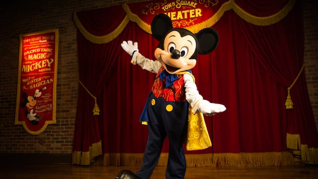 Mickey Mouse with a sign that says Town Square Theater