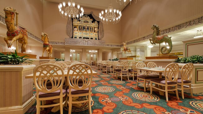 The inside of 1900 Park Fare with set tables, chairs and carousel animals
