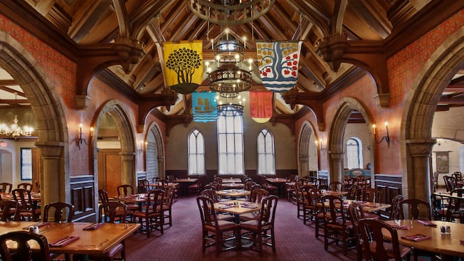 The inside of Akershus Royal Banquet Hall with set tables, chairs and hanging flags with crests
