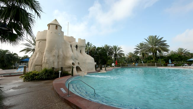 A swimming pool area with a waterslide fashioned to look like a sand castle