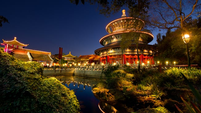 Nighttime view of a pond, verdant grounds and buildings at the China Pavilion