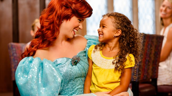 An ecstatic little girl sits on the lap of Princess Ariel at Cinderella's Royal Table