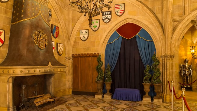 Stone fireplace and curtained gothic archway  with medieval heraldry lining stone walls