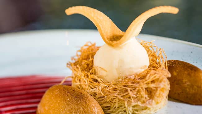 A scoop of ice cream served atop a tuile cookie