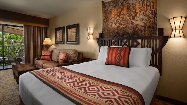 Cama com uma cabeceira rústica, 2arandelas de parede, decoração de parede, sofá, mesinha de café e sacada