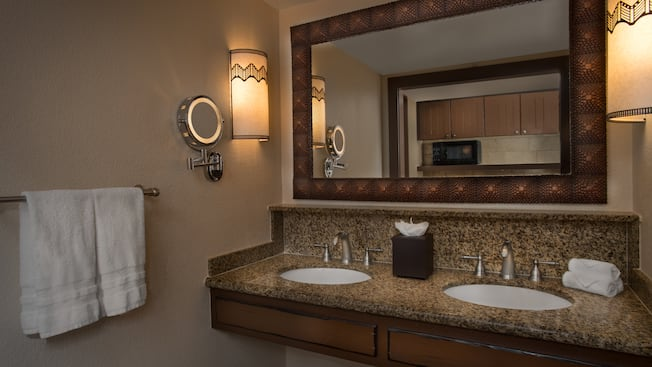 Um gabinete de banheiro com bancada de granito, 2pias, um espelho emoldurado e 2arandelas