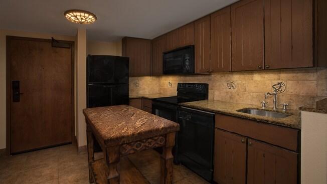 Cozinha com balcão de granito, lava-louças, fogão, forno micro-ondas, geladeira completa e ilha de cozinha