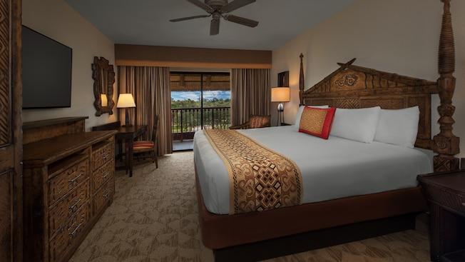 Uma cama, uma luminária sobre mesa de apoio, uma cadeira, uma varanda, uma escrivaninha com cadeira, gaveteiro e TV de tela plana