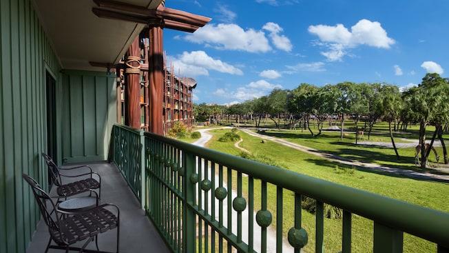 Um pátio ao ar livre com 2cadeiras, uma mesinha e vista das girafas