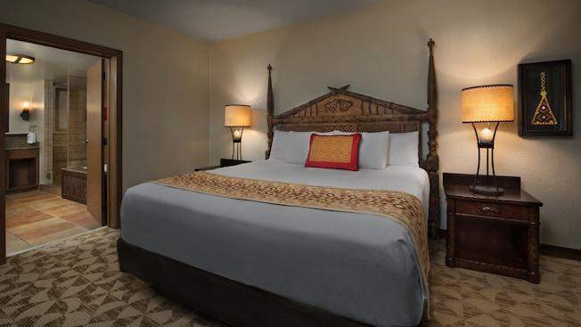 Ladeada por mesas de cabeceira com luminárias, uma cama com almofada e cobertor com tema africano