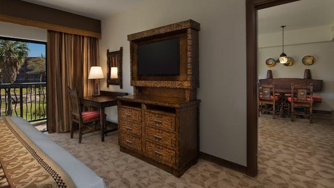 Escrivaninha com tema africano com cadeira, luminária, espelho de parede e cômoda, além de uma TV, em frente a uma cama