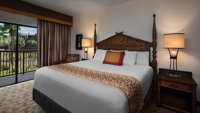 Um quarto com tema africano com uma cama, mesas de cabeceira, luminária de mesa, cadeira, quadro e um pátio ao ar livre