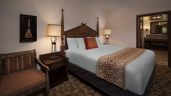 Um quarto com tema africano com uma cama, mesas de cabeceira com luminárias, cadeira e quadro