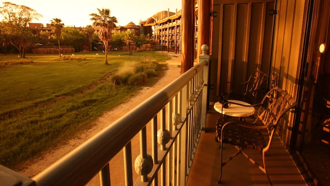 A balcony with 2 chairs and a table, overlooking the savanna