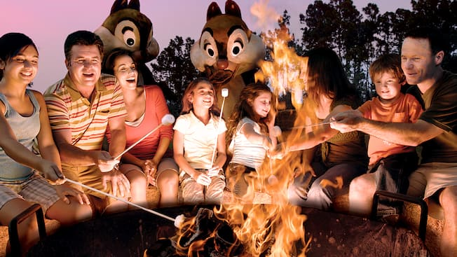 Guests and their kids roasting marshmallows at a campfire with Chip 'n' Dale