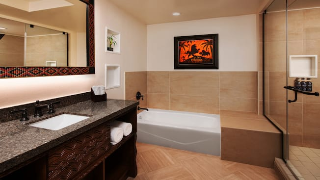 Bathroom with a sink, a vanity, towels, a bathtub and a shower
