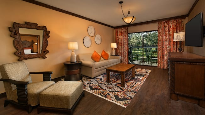 Interior of a room with wood flooring, a dresser, a wall mounted flat screen TV, a mirror, 2 side tables, an upholstered chair with an ottoman, a couch, a coffee table, curtains and a sliding glass door with balcony access