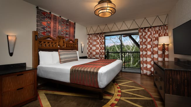 Interior of a room with wood flooring, a dresser, 2 nightstands, a wall mounted flat screen TV, a king bed, curtains and a sliding glass door with balcony access