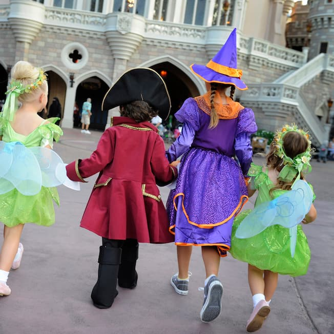 Five costumed children hold hands as they approach Cinderella Castle, including two witches, two fairies and a pirate