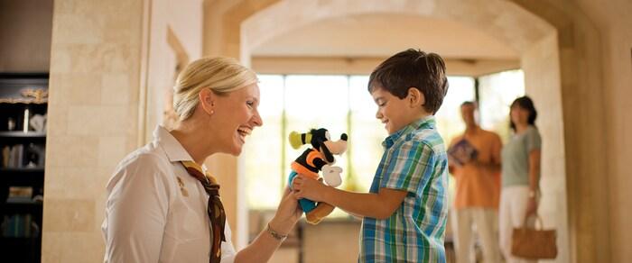 A woman gives a little boy a plush Goofy