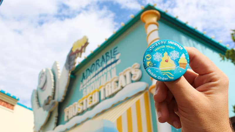 AP Button held in front of the exterior of Adorable Snowman Frosted Treats