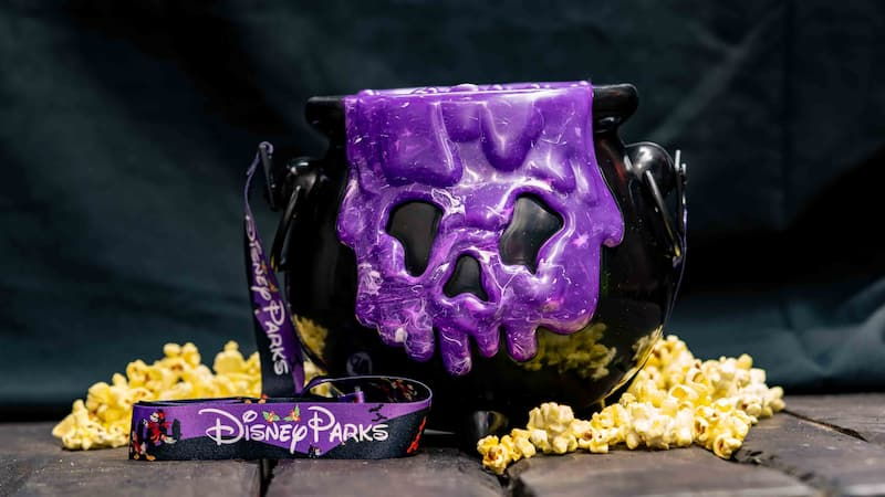 Surrounded by popcorn on a wood table, a cauldron style popcorn bucket features a spooky face oozing over the side with a Halloween themed carry strap that reads Disney Parks