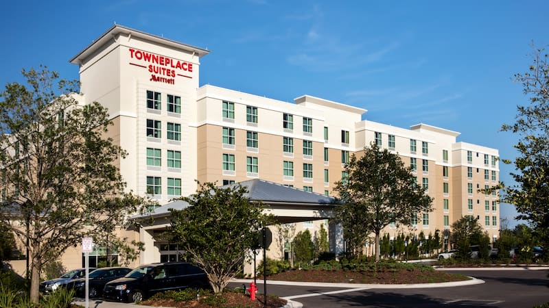 A driveway leads to a low rise hotel with a sign identifying it as the TownePlace Suites Marriott