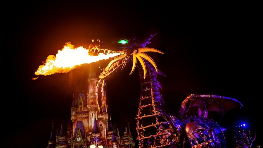 A fire breathing dragon float haunts the night at Magic Kingdom park