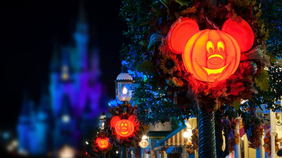 Halloween pumpkin decorations depicting the face of Mickey Mouse adorn light poles on Main Street U S A, with Cinderella Castle in the background