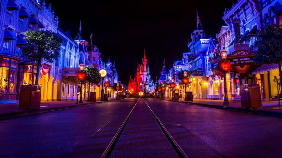 Main Street, U S A, at night, lit with special lighting and adorned with Halloween decorations, with Cinderella Castle in the background