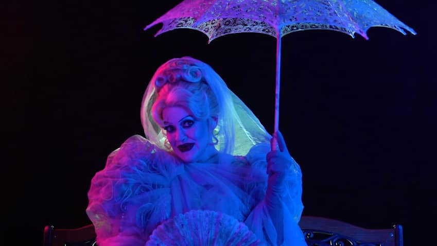 Miss Carlotta, decked out in her last earthly garments and holding a hand fan and an umbrella, sits on a bench as she smiles an other worldly smile