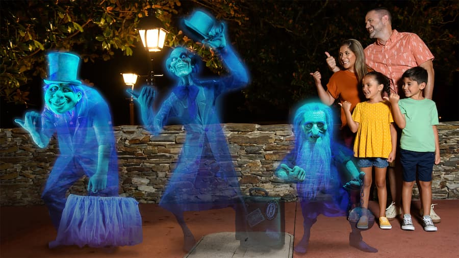 A mom, dad and their two kids give a hitchhiking thumbs up while standing near the three grim grinning ghosts from the Haunted Mansion at night