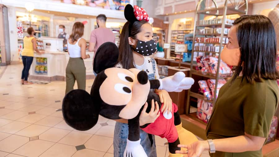 A young girl holding a giant Mickey Mouse plush toy while talking to her mother in the Emporium at Magic Kingdom park