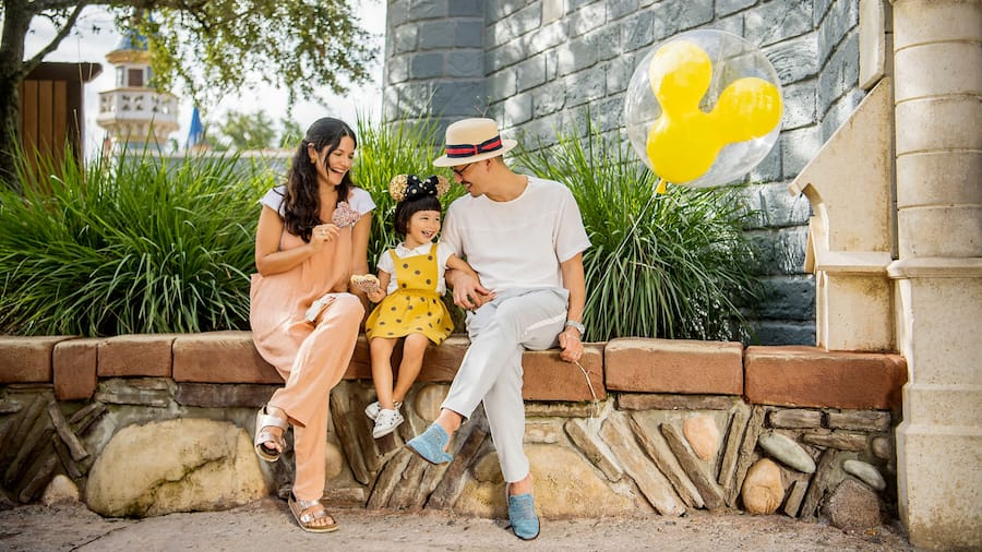 A man, woman and their daughter sitting on a bench with a Mickey Mouse shaped balloon in Magic Kingdom park