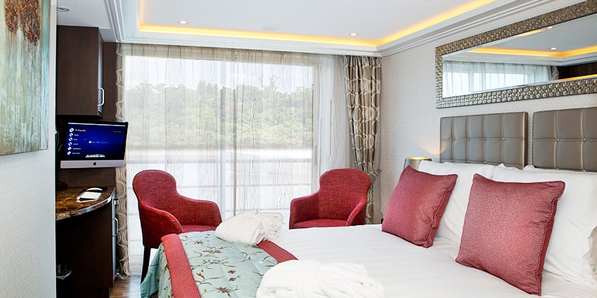 A Category C room, featuring a double bed, two club chairs and a sliding balcony door.