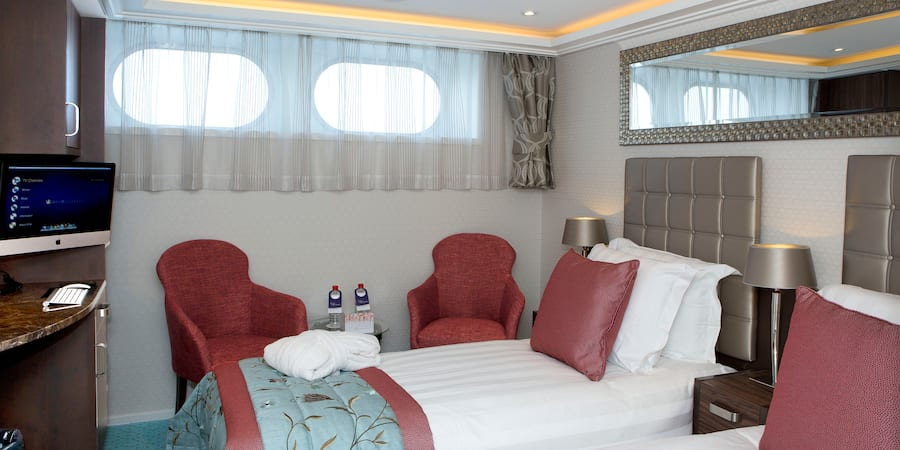 A Category E room, featuring two twin beds, two club chairs and a table.